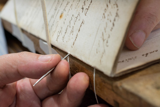 Restoration laboratory. Stitching and binding of an old book, conservation