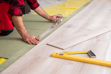 Handyman installing new laminated wooden floor