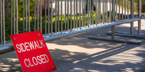 Sidewalk closed sign on a pavement with railing