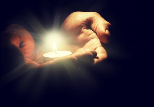 Burning candle in male hand,  religion concept