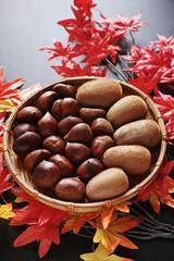 秋の収穫のイメージで、造花のモミジの上にある竹製の笊に入れた栗とキウイフルーツ
