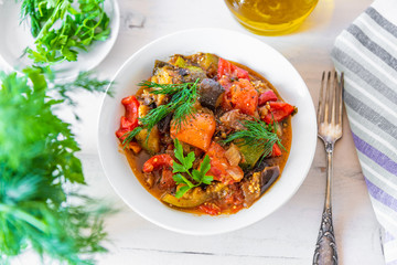 Vegetable stew in a plate on a light rustic wooden background