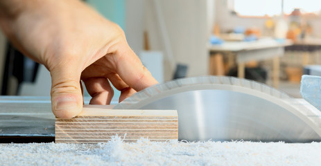 The carpenter cuts the wooden part on the saw. A sharp saw blade is going to cut of a workers thumb. Risk at workplace.