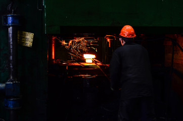 Hot iron in smeltery held by a worker. Iron melting recycling work. Metallurgical production, manufacturing premises, workshop at the plant, blast furnace, heavy industry, engineering, steelmaking.