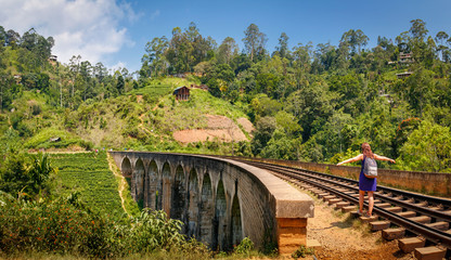 Woman walking on historic Nine Arch Bridge in Ella, Sri Lanka on a sunny day