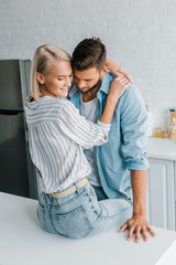 cheerful passionate young couple hugging in kitchen