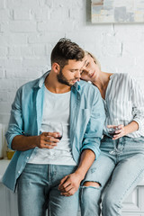 girlfriend holding glass of wine and leaning on handsome boyfriend in kitchen