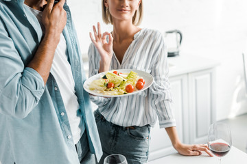 cropped image of girlfriend showing okay gesture to salad in kitchen
