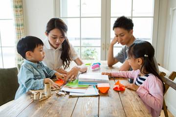 テーブルで遊ぶ家族4人