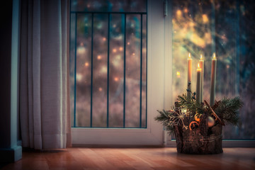 Advent wreath with burning candles at window in dark room. Winter decor interior with warm bokeh lighting. Christmas eve. Cozy Christmas time at home.
