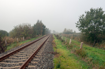 Rusty seemingly endless single track train tracks through a rural Dutch area with early morning fog