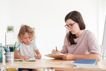 Boy drawing picture while psychologist taking notes during therapy
