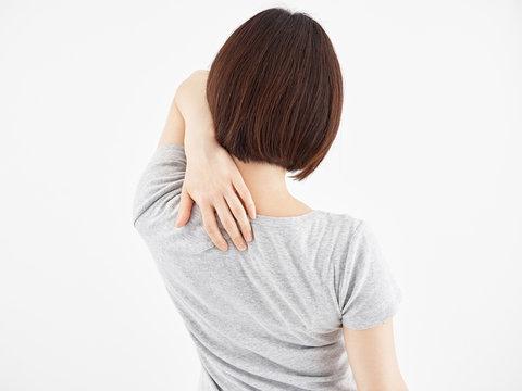 白背景で痛む肩甲骨を押さえる女性