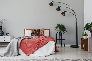Black stylish lamp in elegant bedroom interior with comfortable double bed, plants, and bedside table, real photo with copy space on the wall