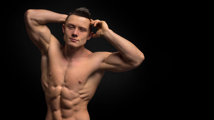 Handsome slim man with muscular body. Closeup of fit young man's abdomen against dark background.
