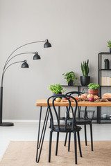 Lamp and plants in grey dining room interior with black chairs at wooden table with food. Real photo