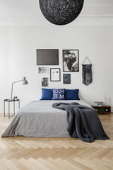 Bedroom with king size bed with blue pillows, grey duvet and blanket, gallery of framed artwork on the wall. Real photo concept