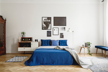 Vintage bedroom interior with bedside table, king size bed with blue bedding and pillows. Mockup gallery on the white wall. Real photo concept