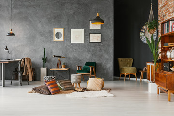 Posters on concrete wall in spacious workspace interior with chair at desk and pillows. Real photo