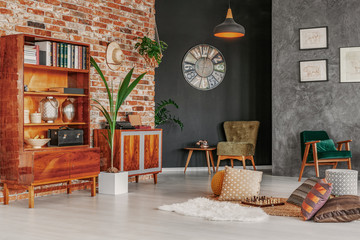 Patterned cushions on the floor and wooden cabinet in grey home office interior with clock. Real photo