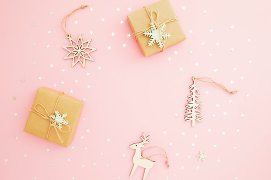 Christmas composition. Gift box, decoration toys and silver confetti on pink background. Flat lay, top view.