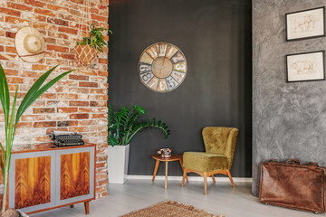 Round clock above table and green armchair in flat interior with plants and wooden cabinet. Real photo