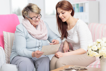 Smiling caregiver watching photos while visiting happy elderly woman at home