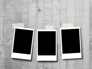 Three blank rectangular instant photo frames on grey concrete wall background