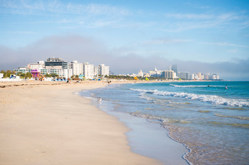 Scenic morning view of waves lapping the shore of an empty South Beach with the city skyline in the background in Miami, Florida, USA