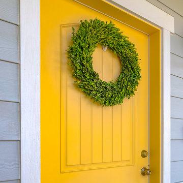 Yellow front door with ornamental green wreath