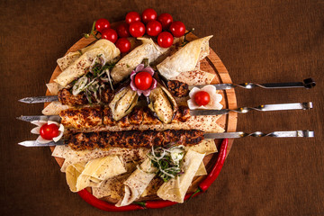 Kebab on skewers on a wooden tray with cherry tomatoes and hot pepper