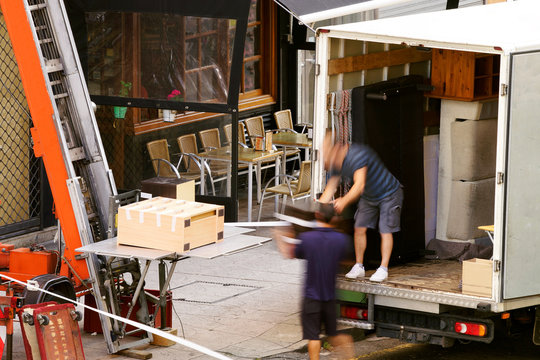 moving company working with elevator in building exterior , workers in motion blur