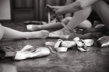 Young ballerina wearing pointe shoes. Close-up of a ballerina's pointe shoes in the dance hall. Vintage photography.