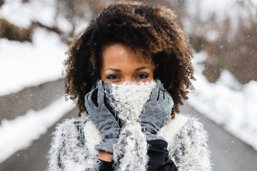Afro hair young woman wearing wool scarf under the snow in winter Wall mural