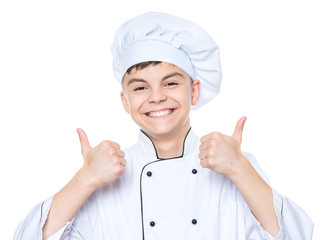 Handsome teen boy wearing chef uniform making thumbs up gesture. Portrait of a happy cute male child cook, isolated on white background. Food and cooking concept.