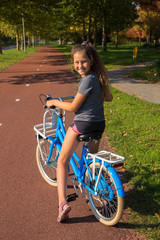 Child rides bike on bike path. Girl is smiling, she is happy.