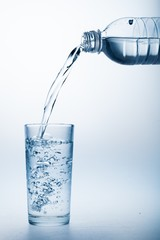 Pouring Water from Bottle into Glass on the Blue Background