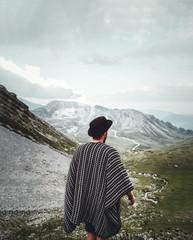 Mann mit Hut und Cape / Poncho steht in den Bergen mit Blick in die Landschaft