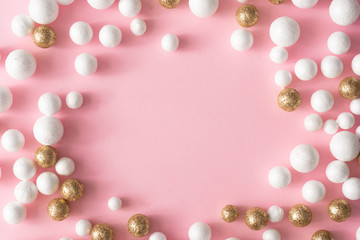 Christmas pink background with copy space made of gold and white glitter ball decoration. New Year...