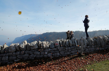 A woman stands on a wall to take a picture during a gust of wind on warm autumn day at the Creux du Van in Val-de-Travers near Neuchatel