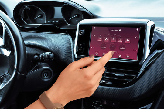 Female driver setting home temperature, safety and environment control on car display