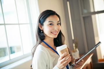 タブレットを持ち仕事をする20代女性