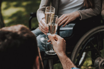 Girl on Wheelchairs with Man on Picnic in Park.