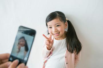 携帯で写真を撮られる女の子
