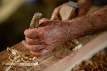 alte Hände mit Holzhobel bearbeiten einen Holzbalken