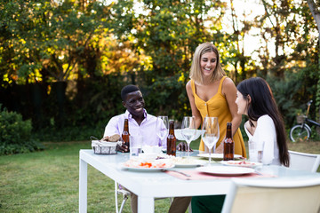 Group of multiethnic man and women sitting at table in beautiful garden enjoying dinner and laughing