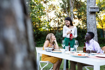 Multiracial women and man sitting at table in green garden having bottle of wine and smiling
