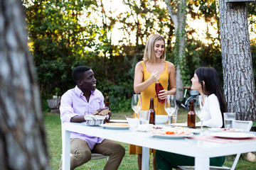 Group of smiling multiracial man and women sitting at table in green garden having bottle of wine and dinner