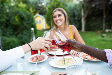Content blond woman having dinner with crop friends in garden clinking with wineglasses and smiling