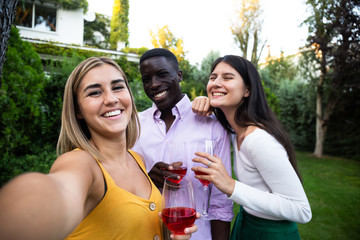 Bright multiethnic women and man having fun in green garden at dinner and taking selfie together